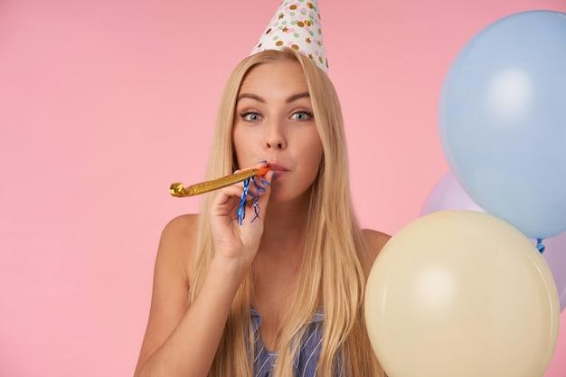 Wewnętrzne zdjęcie pozytywnej długowłosej blondynki świętującej wakacje w stroju imprezowym, pozującej z wielobarwnymi balonami na różowym tle. atrybuty ludzi, rozrywki i wakacji