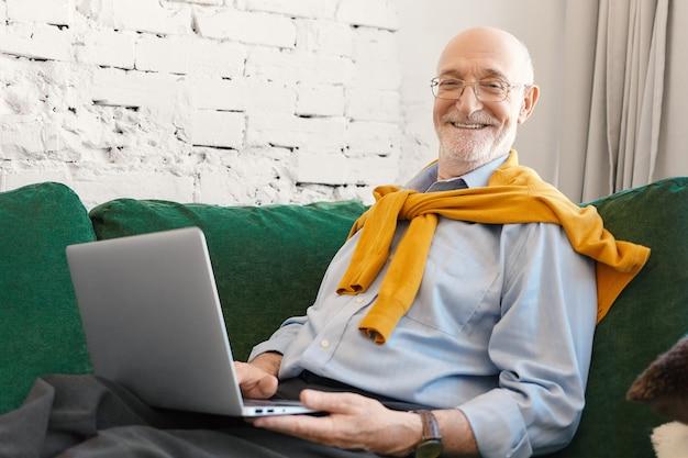 Wewnętrzne zdjęcie pozytywnie atrakcyjnego dziennikarza płci męskiej w okularach i eleganckich ubraniach, pracującego nad artykułem biznesowym do gazety internetowej lub bloga, siedzącego na kanapie z laptopem i uśmiechającego się do kamery