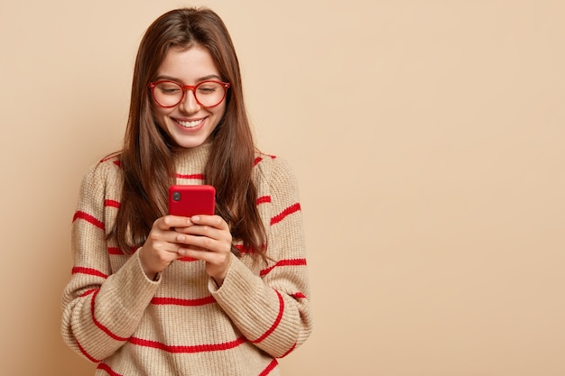 Wewnętrzne zdjęcie zadowolonych nastolatek tekstów przez komórkę, czyta ciekawy artykuł online, nosi swobodny strój, tworzy nową publikację na własnej stronie internetowej, odizolowane na brązowej ścianie z wolną przestrzenią
