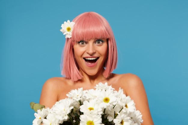 Wewnętrzne zdjęcie zdziwionej, ładnej młodej kobiety z krótką różową fryzurą, patrząc z podekscytowaniem na aparat z szeroko otwartymi ustami, odbierającej kwiaty od tajemniczego chłopaka, odizolowane na niebieskim tle