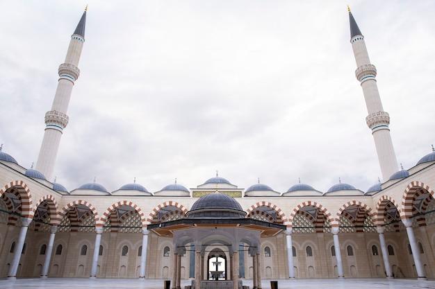 Wewnętrzny dziedziniec meczetu camlica z fontanną i dwiema wieżami, wewnątrz nie ma ludzi, stambuł, turcja