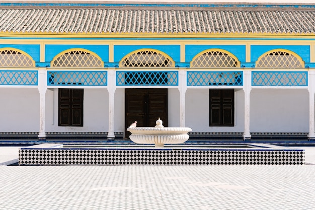 Wewnętrzny dziedziniec otoczony kolumnami z kolorowymi łukami z mozaikami na podłodze i fontanną