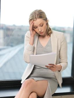 Wewnętrzny obraz zmartwionej kobiety z dokumentami