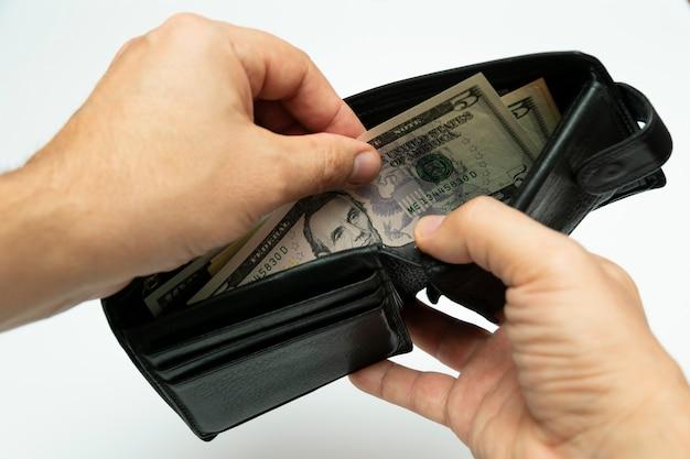 Weź amerykańskie dolary z czarnego skórzanego portfela w jego rękach, zbliżenie