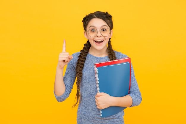Weź książkę z biblioteki. kursy dla uzdolnionych dzieci. szkoła jest fajna. szkolnictwo prywatne. śliczna uśmiechnięta uczennica. dziewczyna mała uczennica. uczeń z warkoczami idzie do szkoły. codzienne życie uczennicy.