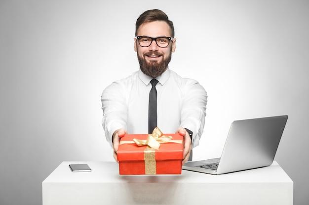 Weź prezent! portret szczęśliwego młodego szefa w białej koszuli i czarnym krawacie siedzi w biurze i daje ci czerwone pudełko, gratuluję wakacji. wewnątrz, na białym tle, studio strzał, szare tło