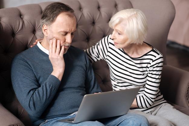 Weź tabletkę. dość starsza kobieta wspiera swojego męża, który ma silny ból zęba podczas korzystania z laptopa.