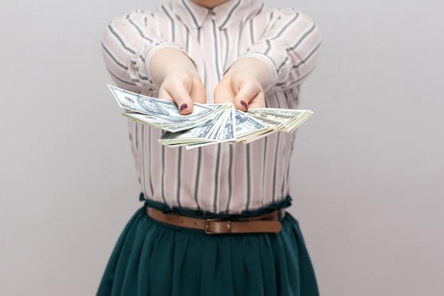 Weź to! bliska portret udanej kobiety w stojącej koszuli w paski, trzymając wiele dolarów, fanem demonstracji pieniędzy. wewnątrz, studio strzał, na białym tle, szare tło