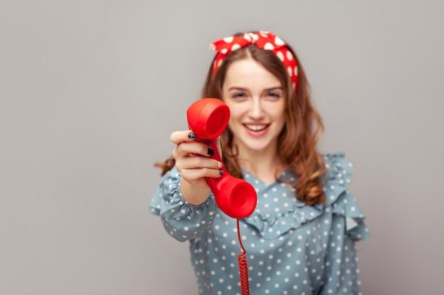 Weź to, odbierz telefon! szczęśliwa dziewczyna pinup dająca telefon patrząc na kamerę, uśmiechnięta