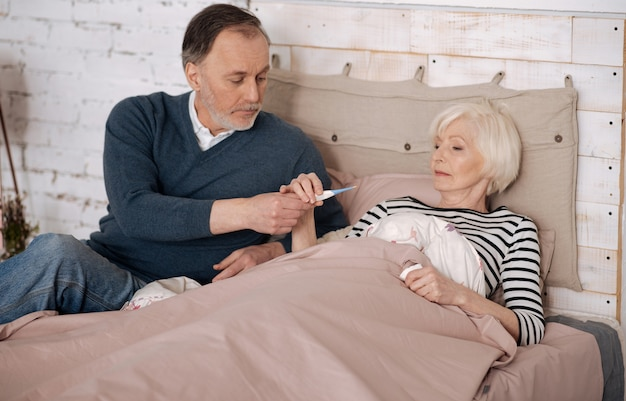 Weź to. starszy przystojny mężczyzna daje termometr swojej starszej chorej żonie, leżąc na łóżku przykrytym ciepłym kocem.