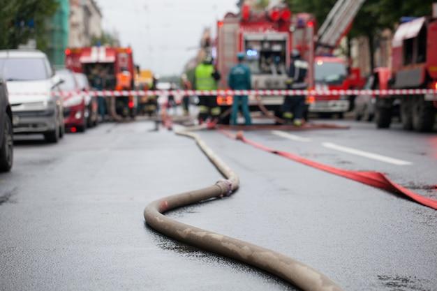 Węże pożarnicze na tle wozów strażackich.