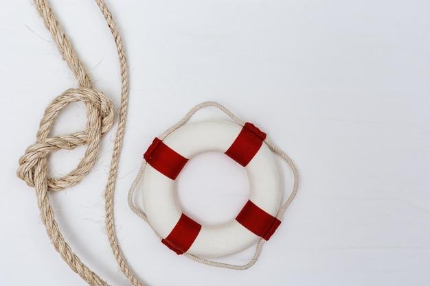 Węzeł liny morskiej, koło ratunkowe i muszle. widok z góry.