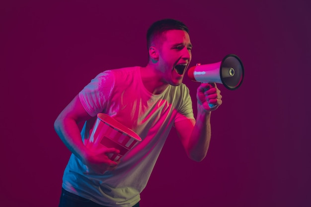 Wezwanie do sprzedaży, krzyki. kaukaski portret mężczyzny na białym tle na różowo-fioletowej ścianie w świetle neonów. model męski z urządzeniami. pojęcie ludzkich emocji, wyraz twarzy,