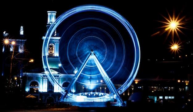 Wheel of view at kontraktova square, kijów. miasto nocą. ścieśniać