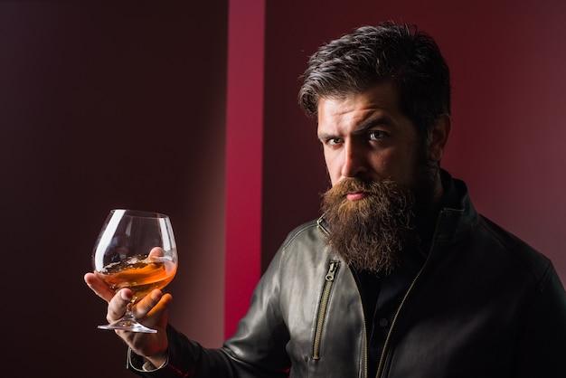 Whisky brandy mocny alkohol brutalny mężczyzna smakuje degustację whisky i degustuje mężczyznę w skórze