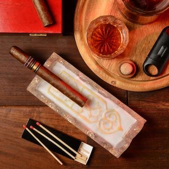 Whisky, cygara i popielniczka na drewnianym stole. widok z góry