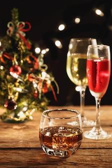 Whisky i koktajl w boże narodzenie na drewnianym stole