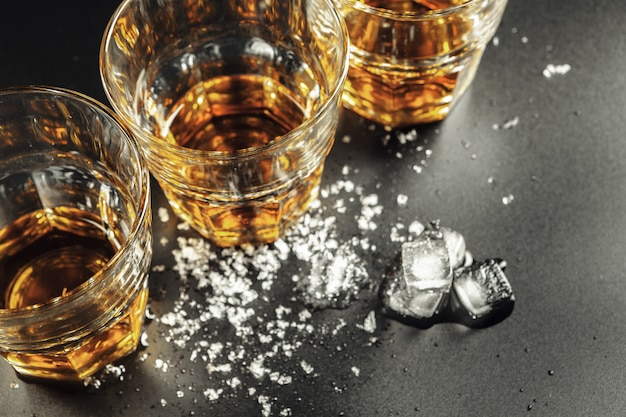 Whisky i lód na nieociosanym drewnianym tle