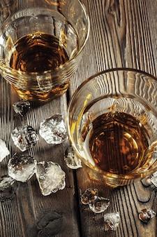 Whisky i lód na rustykalnym drewnie