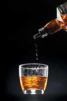 Whisky leje do szklanki na czarnym tle