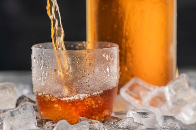 Whisky lub bourbon w matowej szklance z lodem. napój alkoholowy.