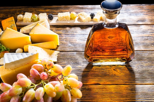 Whisky lub brandy w nowoczesnej stylowej karafce na stole bufetowym z bukietem serów na półmisku i kiścią świeżych winogron