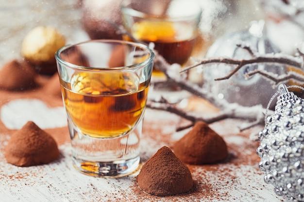 Whisky lub likier, cukierki czekoladowe truflowe w proszku kakaowym i ozdoby świąteczne na białym tle drewnianych.