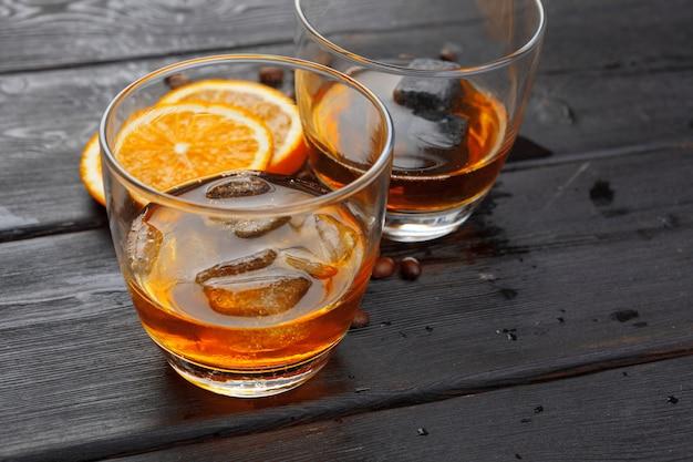 Whisky lub likier, ziarna kawy i pomarańcza cięte na drewnie. sezonowe wakacje.