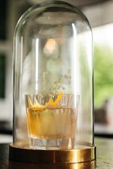 Whisky & smoke. jesienna stara moda z pomarańczą i tymiankiem. eksperymentalny koktajl alkoholowy w kolbie z dymem