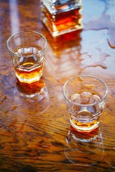 Whisky stara kwadratowa karafka z dwoma szklankami na lakierowanym blacie