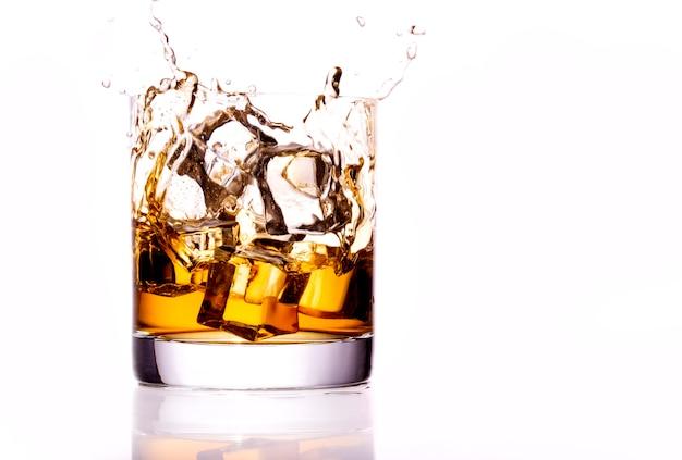 Whisky szkło z pluśnięciem, odosobnionym na białym tle