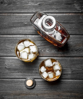 Whisky w butelce i szklankach. na czarnym drewnianym stole