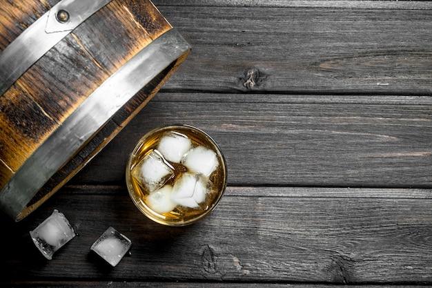 Whisky w szklance z kostkami lodu i beczką. na drewnianym