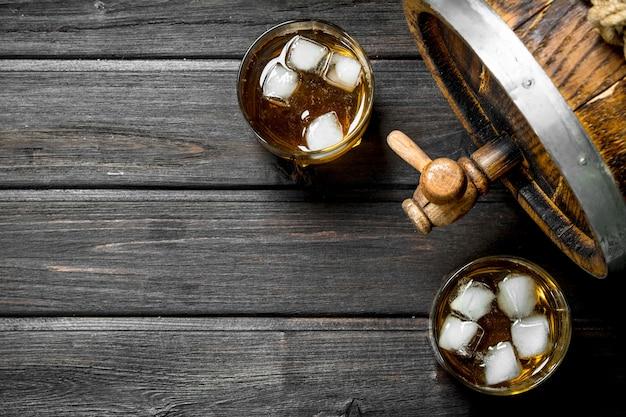 Whisky w szklankach z lodem i drewnianą beczką. na drewnianym stole