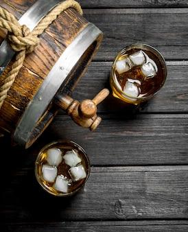 Whisky w szklankach z lodem i drewnianą beczką. na drewnianym