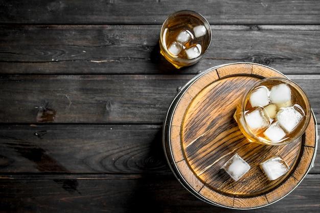 Whisky w szklankach z lodem na beczce.