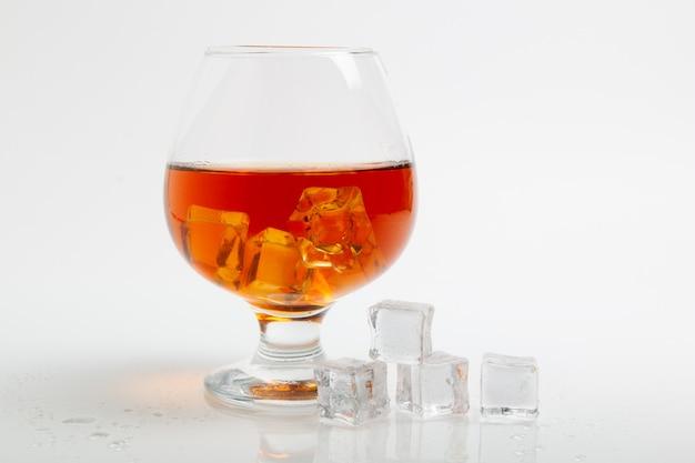 Whisky w szkle i kostce lodu na białym tle
