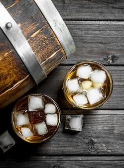 Whisky z lodem i drewnianą beczką. na czarnym drewnianym