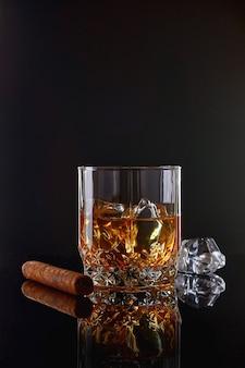 Whisky z lodem lub brandy w szkle z cygarem na czarnym stole. whisky z lodem w szkle. whisky lub brandy. selektywna ostrość.