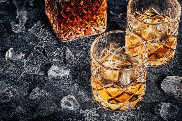 Whisky z lodem na ciemnym tle kamienia.