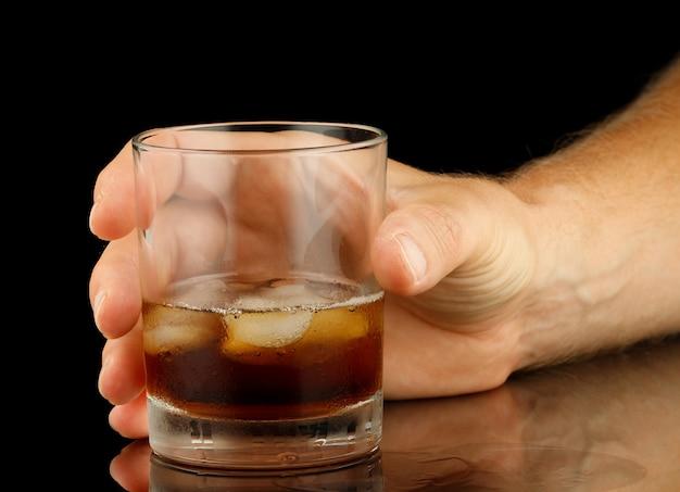 Whisky z lodem w ręku na białym tle
