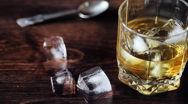 Whisky z lodem ze szklanką. kostki lodu na drewnianym stole i szklanka ze schłodzonym mocnym alkoholem. stolik z amerykańską whisky, bourbonem i kartami.