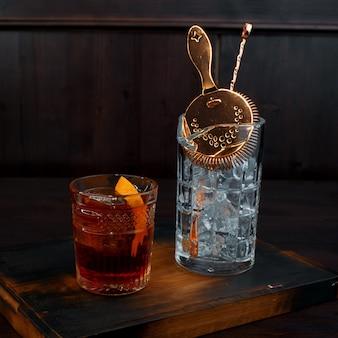Whisky z plastrem pomarańczy w kryształowym kieliszku stoi na stole w barze obok kieliszka z lodem i profesjonalnym narzędziem do robienia koktajlu. mocny napój korzenny.