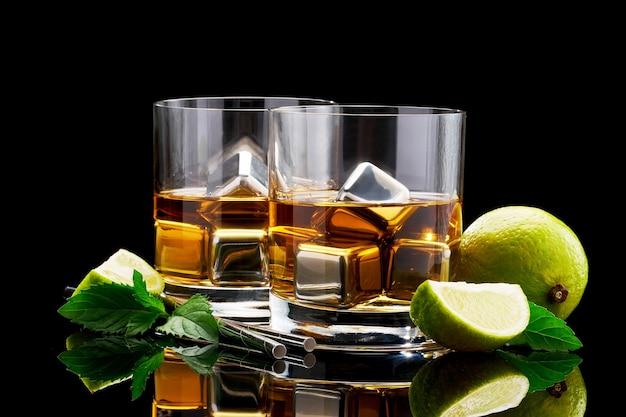 Whisky ze stalowymi kostkami chłodzącymi na ścianie z ciemnego szkła