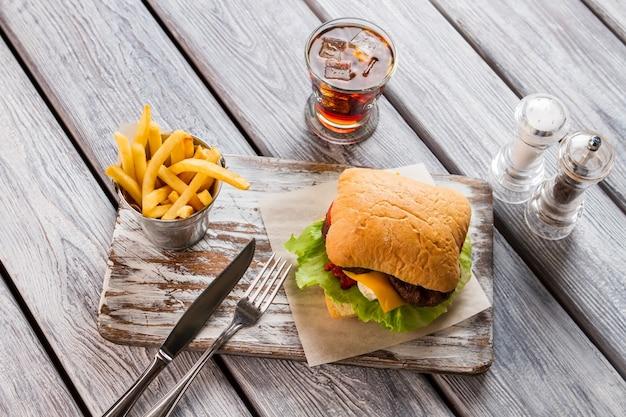 Wiaderko frytek i hamburgera. nóż z widelcem na pokładzie. przykład niezdrowej żywności. burger wołowy i cola.