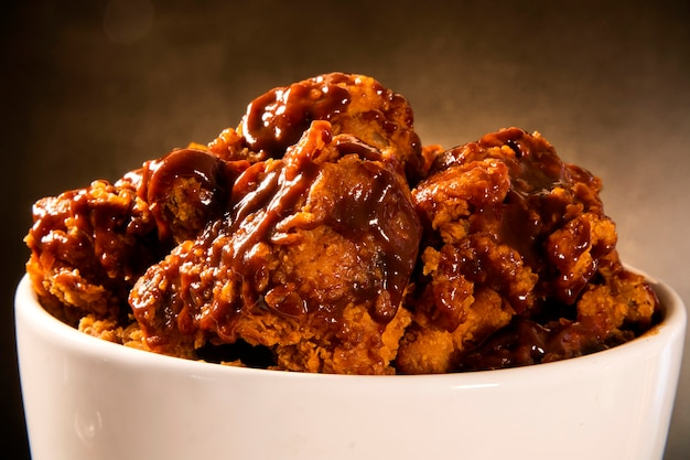 Wiaderko pełne chrupiącego smażonego kurczaka kentucky z dymem i sosem barbecue na brązowym tle. selektywna ostrość.