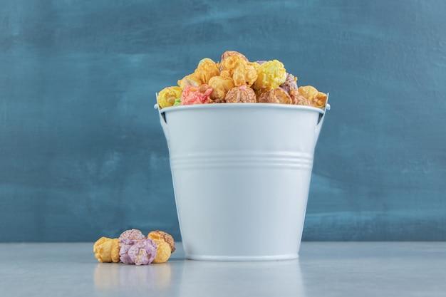 Wiaderko pełne słodkiego, różnokolorowego popcornu.