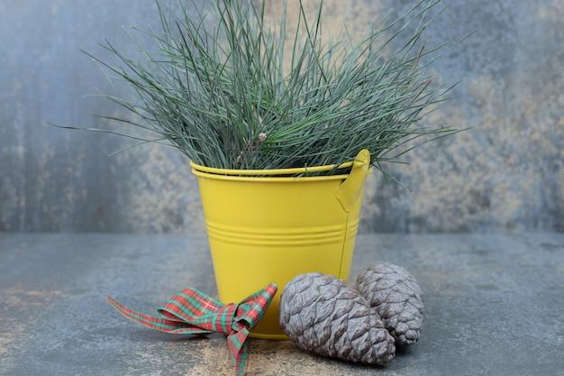 Wiaderko trawy ozdobione kokardką i szyszkami na marmurowym stole. wysokiej jakości zdjęcie