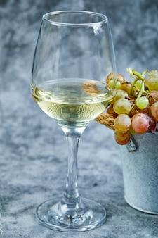 Wiaderko winogron i kieliszek wina na niebieskiej powierzchni.