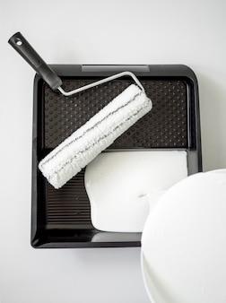 Wiaderko z białą farbą i wałek do pędzla z kuwetą